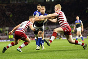 Rob Burrow of Leeds Rhinos is tackled by George Williams and Liam Farrell of Wigan Warriors during the First Utility Super League Grand Final between Leeds Rhinos and Wigan Warriors at Old Trafford on October 10, 2015 in Manchester, England.