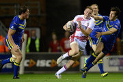 Joe Burgess of Wigan Warriors gets past Ben Harrison and Stefan Ratchford of Warrington Wolves during the First Utility Super League Qualifying Semi-Final match between Wigan Warriors and Warrington Wolves at DW Stadium on October 3, 2014 in Wigan, England.