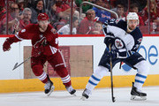 T.J. Galiardi #21 of the Winnipeg Jets skates with the puck ahead of Sam Gagner #9 of the Arizona Coyotes during the NHL game at Gila River Arena on October 9, 2014 in Glendale, Arizona. The Jets defeated the Coyotes 6-2.