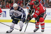 Marian Hossa #81 of the Chicago Blackhawks and T.J. Galiardi #21 of the Winnipeg Jets battle for the puck at the United Center on November 2, 2014 in Chicago, Illinois.