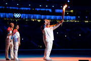 Russian former wrestler Alexander Karelin holds up the Olympic torch next to Russian pole vaulter Yelena Isinbayeva (2nd L) and Russian tennis player Maria Sharapova (L) during the opening ceremony of the Sochi 2014 Winter Olympics at the Fisht Olympic Stadium on February 7, 2014, in Sochi, Russia.