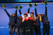 Gold medallists Kaillie Humphries (3rdL) and Heather Moyse (3rdR) of Canada team 1 pose on the podium with silver medallists Elana Meyers (L) and Lauryn Williams (2ndL) of the United States team 1 and bronze medallists Jamie Greubel (2ndR) and Aja Evans of the United States team 2 during the flower ceremony during the Women's Bobsleigh on Day 12 of the Sochi 2014 Winter Olympics at Sliding Center Sanki on February 19, 2014 in Sochi, Russia.