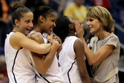 (L-R) Caroline Doty #5, Maya Moore #23, Tiffany Hayes #3 and associate coach Chris Dailey of the Connecticut Huskies celebrate following their victory over the Baylor Bears during the Women's Final Four Semifinals at the Alamodome on April 4, 2010 in San Antonio, Texas. Connecticut defeated Baylor 70-50.