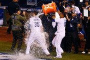 Salvador Perez #13 of the Kansas City Royals douses Eric Hosmer #35 of the Kansas City Royals after defeating the New York Mets 5-4 in Game One of the 2015 World Series at Kauffman Stadium on October 27, 2015 in Kansas City, Missouri.