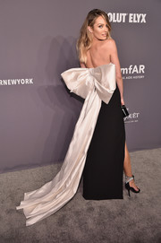Candice Swanepoel attended the 2019 amfAR New York Gala wearing a strapless black Rasario gown with an oversized white bow at the back.