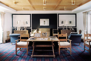 Plaid carpeting and coffered ceilings in an open living space