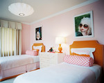 Kids' Room - Large-scale photographs above orange upholstered headboards and pink bolster pillows