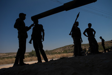 2013 Members of the Free Syrian Army chat in front of a T-72 tank, parked in a secret location close to al-rami village