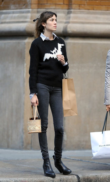 British model Alexa Chung, wearing a black bat sweater and carrying a small woven basket, gives the thumbs up as she crosses the street while out and about in Soho, New York City.