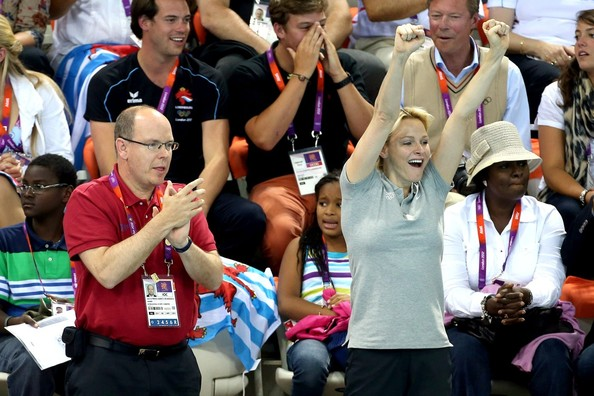 Princess Charlene of Monaco, a former South African Olympic swimmer herself, joins Chad le Clos' parents for the medal ceremony