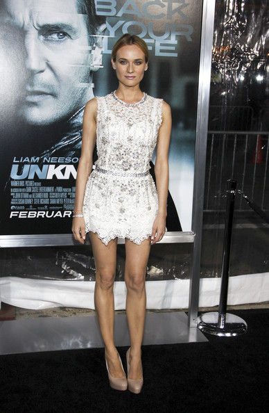 "Diane Kruger at the Los Angeles premiere of ""Unknown"" held at the Regency Village Theatre, Los Angeles. She was wearing a white lace Dolce & Gabbana Spring 2011 dress. Her embellished mini dress is simply styled with a pulled back hairstyle, glossy lips and nude Brian Atwood pumps.."