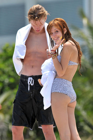 "Bella Thorne, star of the Disney show ""Shake It Up!"", shows off her beach body in a high waisted bikini while soaking up the sun with boyfriend Tristan Klier on the beach in Miami."