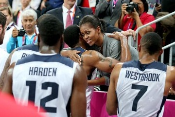 First Lady Michelle Obama cheers on the USA Basketball Dream Team before the players spontaneously hug her after winning against France in the Summer Olympics