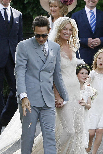 LAST SMOKE: Jamie Hince puts out his cigarette as he and his new bride, Kate Moss, pose with their 15 bridesmaids following their wedding ceremony .