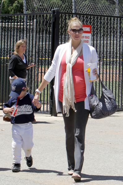 A pregnant Victoria Prince holds hands with Sean Preston after his little league baseball game.