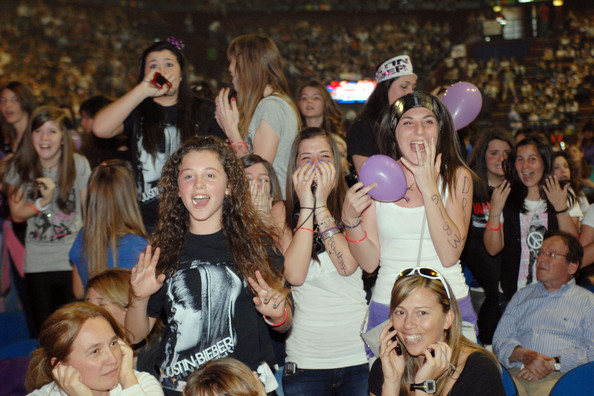 "Justin Bieber fever breaks out in Italy! Thousands of screaming girls (and a few embarrassed-looking dads!) watched their idol perform songs on his ""My World"" tour. On stage, Bieber appeared to using a few of Michael Jackson's classic moves. The 17-year-old was seen grabbing his crotch, standing with his arms outstretched and wearing bandages on two of his fingers."