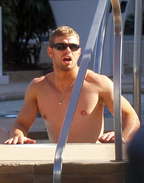 Actor Kellan Lutz shows off his famous physique as he relaxes poolside in Miami with friends.