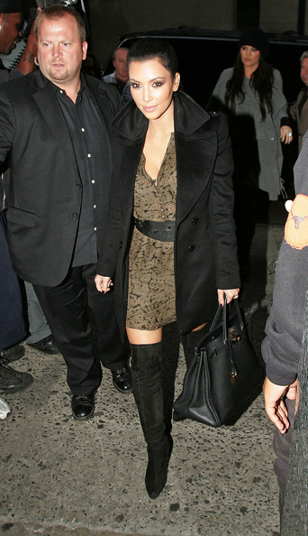Kim Kardashian Kim Kardashian returns to her hotel wearing a black coat and olive green cinched dress in NYC.