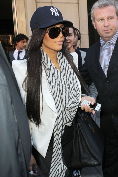 Kim Kardashian, wearing a New York Yankees hat and a rather large ring, leaves her New York City hotel with her sister Kourtney. The sisters reportedly hopped into a SUV which was loaded with their luggage.
