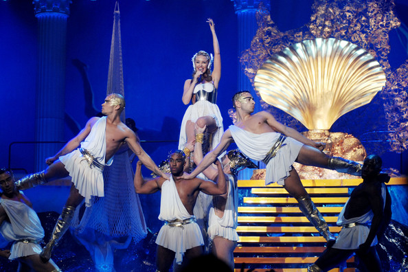 Kylie Minogue Kylie Minogue performs live at the Mediolanum Forum in Milan on her 'Aphrodite - Les Folies' 2011 tour. The Australian singer was dressed in a white and gold outfit and emerged from a giant golden shell on to the stage.
