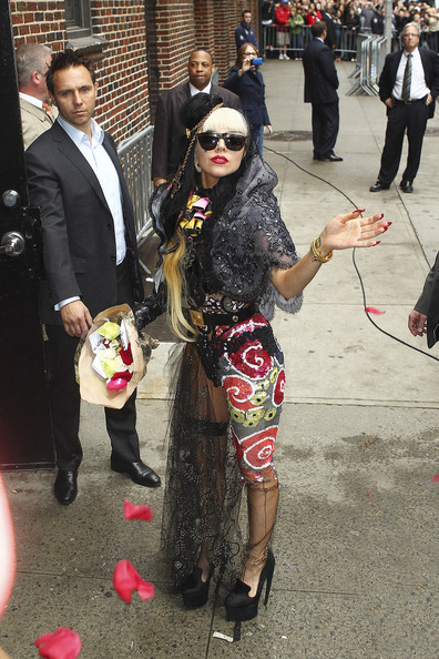 "Lady Gaga FLOWERS FROM GAGA: The ""Born This Way"" singer arrives at the ""Late Show David Letterman,"" throwing flowers up in the air to her fans. The singer is seen wearing a lacy, veiled outfit, with retro glasses and a sequined piece wrapped around her left leg, resembling what looks like roses."
