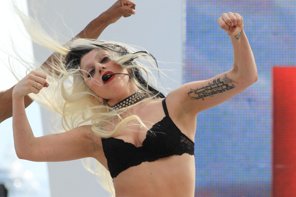 "Lady Gaga Ra-Ra! Lady Gaga performs at the ""Grand Journal"" TV Show in Cannes during Cannes Film Festival. The daring live performer is seen with two-tone black-blonde hair and a black bra as she performs onstage, showing off her tattooed left arm while dancing."
