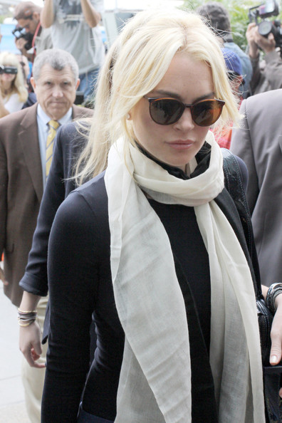 Lindsay Lohan A modestly dressed Lindsay Lohan - in a long sleeve black shirt and white scarf - arrives in court for her preliminary hearing regarding an alleged stolen necklace.