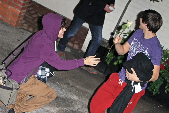 "Louis Tomlinson Niall Horan of One Direction cheekily takes a rose from bandmate Louis Tomlinson following ""The X Factor"" rehearsals."