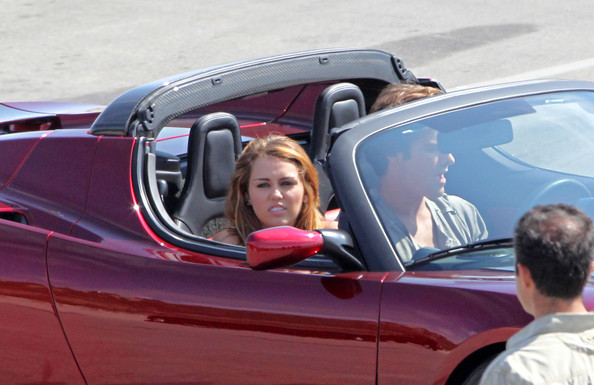Miley Cyrus Miley Cyrus rides in the passenger seat of a red Tesla roadster electric car, with a pricetag of over $129,000, as part of a photoshoot in LA. The pop singer had her makeup crew and assistants on hand, wearing a beige dress cinched with a belt and platform strappy heels.