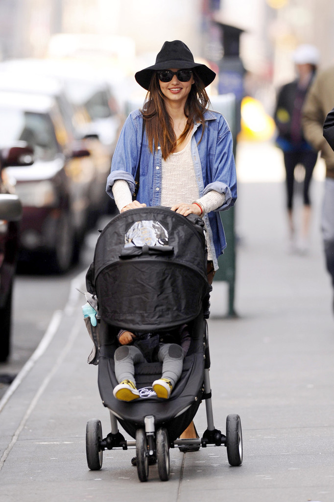 Miranda Kerr flashes a smile as she pushes her baby boy Flynn in a stroller in New York City. The Australian model, who is married to actor Orlando Bloom, looked beautiful as she strolled down the busy street.