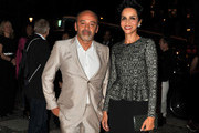 Farida Khelfa and Christian Louboutin arrive for the  Azzedine Alaia Fashion Show  at museum of modern art during Paris Fashion Week in Paris.
