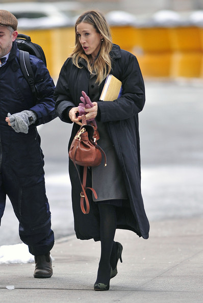 "Sarah Jessica Parker seen filming ""I Don't Know How She Does It ""on Wall Street in New York City. The always fashionable actress is seen looking to be in great spirits, smiling with co-star Olivia Munn in between takes. Donning a long grey trench coat, Parker stayed warm with pink gloves and an extra thick parka jacket during breaks. Written on her character's right hand are the words 'bouncy house'."
