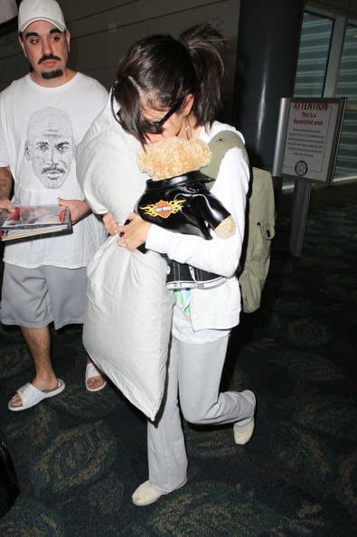 Selena Gomez Former Disney star Selena Gomez is seen attracting attention as she arrives at Miami Airport. The actress clutches a pillow and a Harley Davidson teddy bear as she tries to cover up from photographers. Gomez was recently surprised by pop star boyfriend Justin Bieber on her 22nd birthday by appearing at her concert in California.