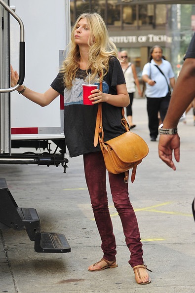 Clemence Poesy looking dressed down in burgundy tie dye jeans and a loose t-shirt on the set of