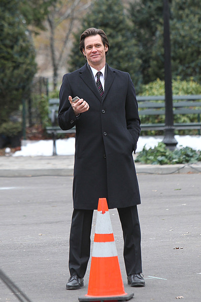 "Jim Carrey films a scene for his upcoming comedy ""Mr. Popper's Penguins"" in Central Park, NYC. The actor wearing a business trench coat, is seen hiding his iPhone in his hands before filming resumes."
