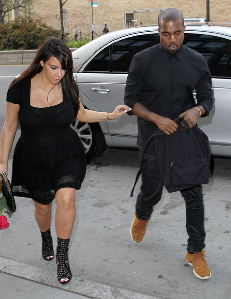 A somber looking Kim Kardashian receives a red rose from Kanye West as they head out in New York City.